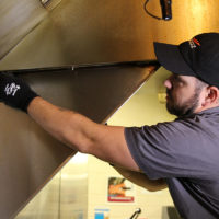 HOODZ kitchen cleaning franchise tech cleaning a hood